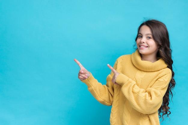 Retrato sonriente joven de la muchacha que señala Foto gratis