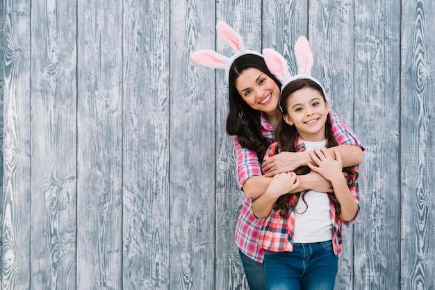 Retrato sonriente de madre abrazando a su hija por detrás frente a fondo de madera Foto gratis