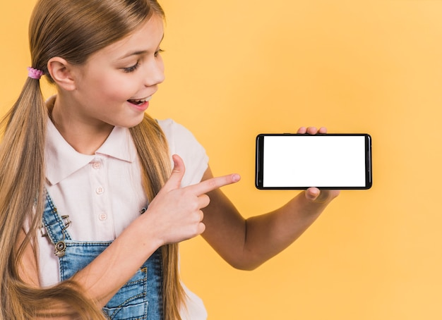 Retrato sonriente de una muchacha con el pelo rubio largo que señala en el teléfono móvil que muestra la pantalla en blanco blanca Foto gratis