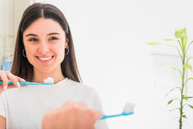 Retrato sonriente de una mujer joven en el espejo que sostiene el cepillo de dientes en la mano Foto gratis