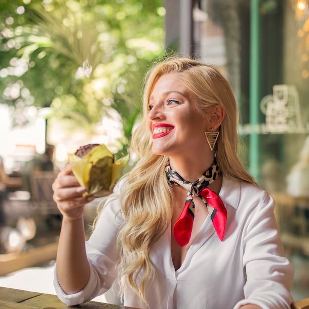 Retrato sonriente de una mujer joven que sostiene el mollete en la mano que mira lejos Foto gratis
