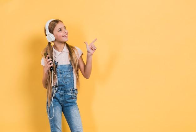 Retrato sonriente de una música que escucha de la muchacha en el auricular que señala en algo contra fondo amarillo Foto gratis