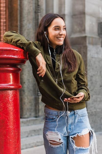 Retrato sonriente de una música que escucha de la mujer joven en el teléfono que se coloca en la calle Foto gratis