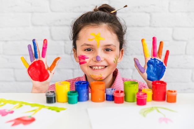 Retrato sonriente de una niña detrás de la mesa con botellas de pintura que muestran su mano y rostro pintados con colores Foto gratis