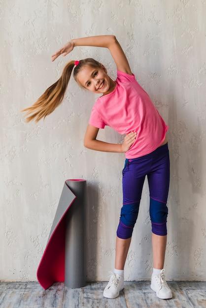Retrato sonriente de una niña haciendo ejercicios de estiramiento frente a un muro de hormigón Foto gratis