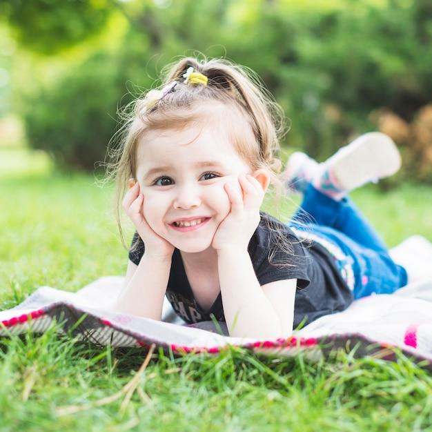 Retrato de sonriente niña hermosa acostada en una manta en el jardín Foto gratis