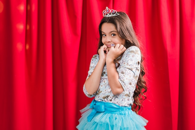 Retrato de sonriente niña linda tímida de pie delante de la cortina roja Foto gratis