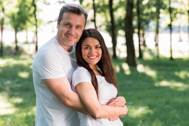 Retrato de sonriente pareja amorosa en el parque Foto gratis