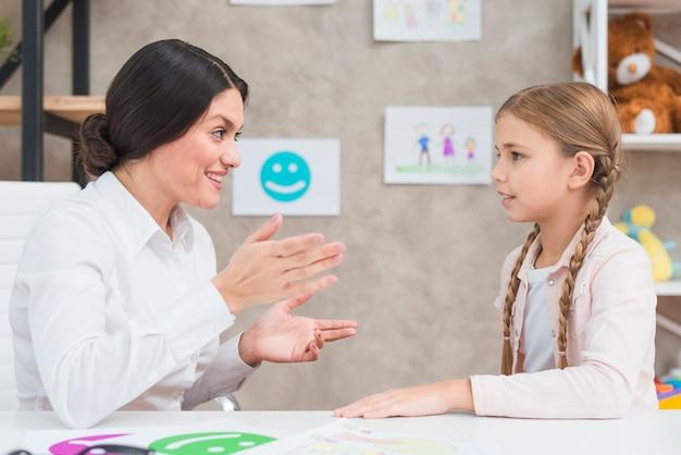 Retrato sonriente de una psicóloga y una niña que tiene una conversación en la oficina Foto gratis