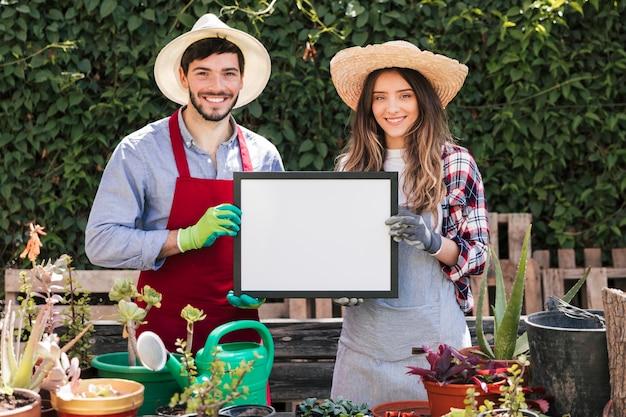 Retrato sonriente de un sombrero que lleva del jardinero de sexo masculino y de sexo femenino que muestra el marco en blanco blanco en el jardín Foto gratis