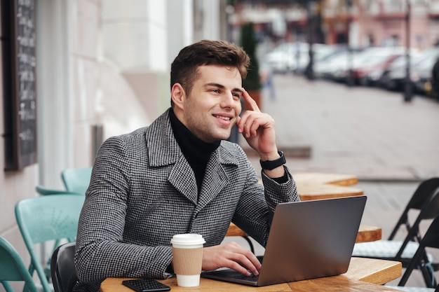 Retrato de un tipo exitoso que trabaja con una computadora portátil plateada en un café callejero, piensa en negocios o chatea con un amigo Foto gratis
