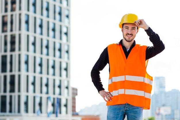 Retrato del tiro medio del arquitecto sonriente que mira la cámara Foto gratis