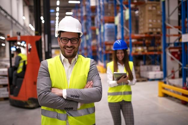 Retrato de trabajador de almacén exitoso o supervisor con los brazos cruzados de pie en una gran área de distribución de almacenamiento Foto gratis