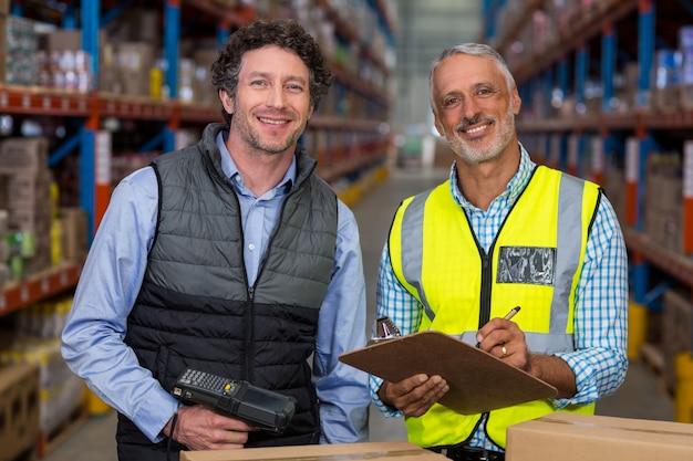 Retrato de trabajadores de almacén con portapapeles y escáner de código de barras Foto Premium