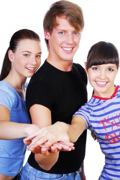 Retrato de tres hermosos jóvenes adultos con las manos apiladas uno encima del otro Foto gratis