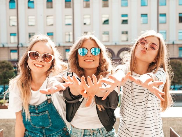Retrato de tres jóvenes hermosas chicas hipster sonrientes en ropa de moda de verano. mujeres despreocupadas sexy posando en la calle. modelos positivos divirtiéndose en gafas de sol. muestran sus palmas Foto gratis