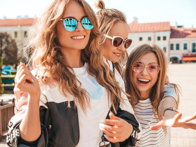 Retrato de tres jóvenes hermosas chicas hipster sonrientes en ropa de moda de verano. mujeres despreocupadas sexy posando en la calle. modelos positivos divirtiéndose en gafas de sol. Foto gratis
