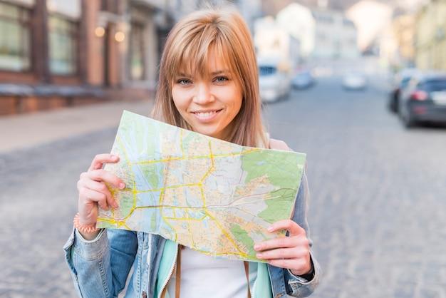 Retrato de un turista femenino sonriente que se coloca en la calle que muestra el mapa Foto gratis