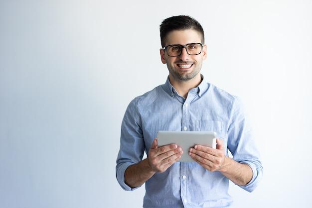 Retrato del usuario emocionado alegre de la tableta que lleva las lentes Foto gratis
