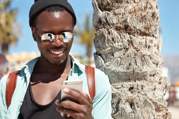 Retrato de verano al aire libre del alegre chico de piel oscura con ropa de moda usando un teléfono celular, disfrutando de la comunicación en línea con amigos a través de redes sociales, mensajes, enviando fotos durante un viaje al extranjero Foto gratis