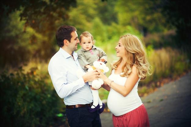 Retrato de verano de familia feliz. madre embarazada, padre e hija pequeña. Foto Premium