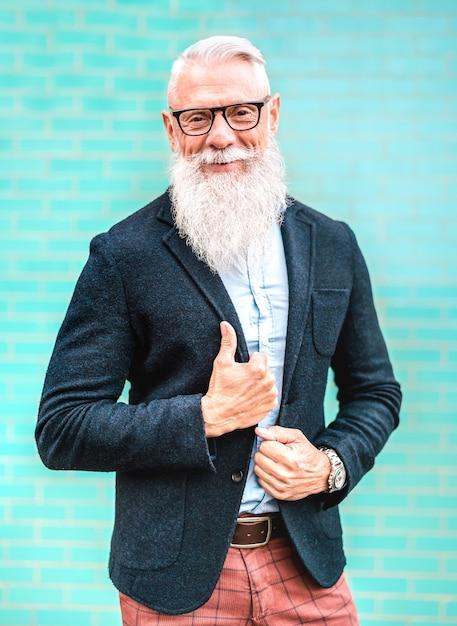 Retrato vertical de hombre hipster con elegante traje posando sobre fondo de pared turquesa Foto Premium