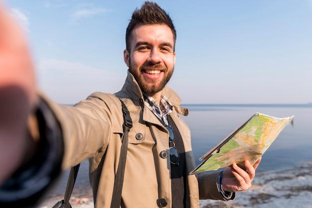 Retrato de un viajero masculino joven sosteniendo un mapa en la mano tomando selfie Foto gratis