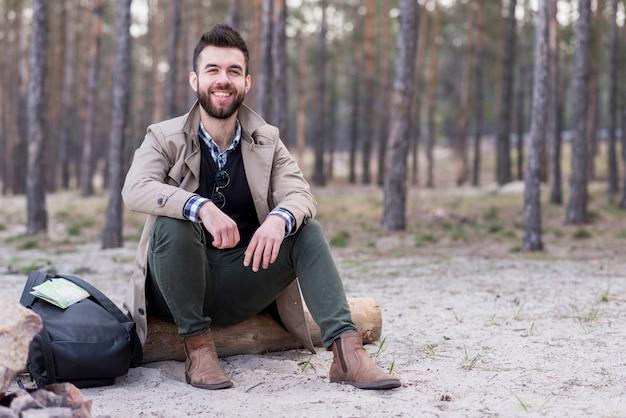 Retrato de un viajero masculino sonriente sentado en la playa con su mochila Foto gratis