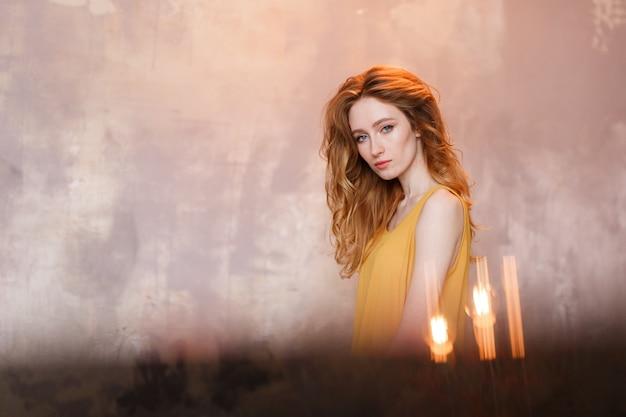 Retrato de la vista delantera de la mujer joven hermosa que desgasta contra la pared gris del desván. Foto gratis