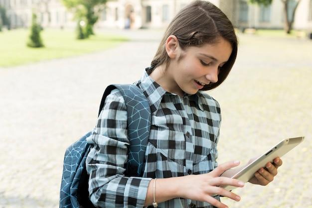 Retrato de vista lateral de chica de secundaria usando tableta Foto gratis