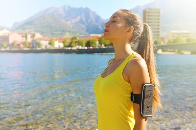 Retrato de vista lateral de una mujer fitness con brazalete para teléfono inteligente relajante respirar aire fresco en el lago de la ciudad por la mañana. copie el espacio. Foto Premium