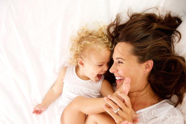 Retrato de vista superior de la feliz madre e hija acostada en la cama en casa Foto Premium