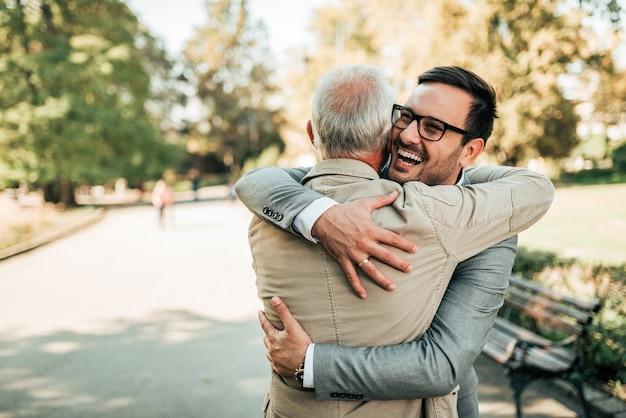 Reunión familiar. padre e hijo abrazando al aire libre. Foto Premium