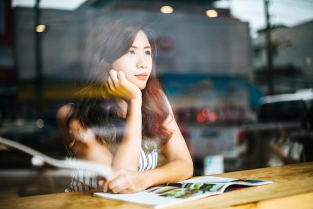 Revista hermosa de la lectura de la mujer en café Foto gratis
