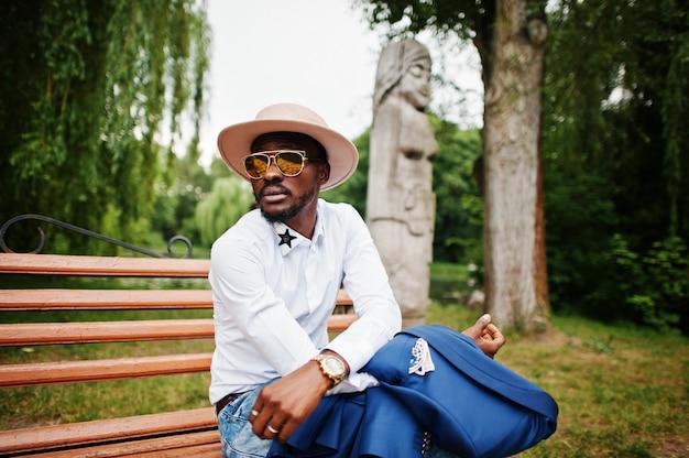Rico hombre negro sentado en el banco en gafas de sol doradas y sombrero Foto Premium