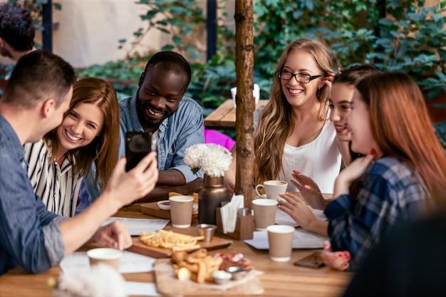 Riendo y charlando en la reunión de afterworks con compañeros de trabajo en el pequeño y acogedor café local. Foto gratis