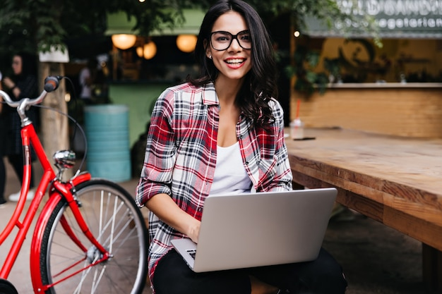Riendo a chica latina de pelo negro posando con bicicleta y portátil. señora elegante feliz con la computadora sentada en la calle. Foto gratis