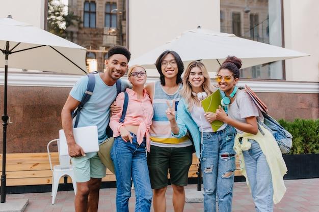 Riendo a un niño asiático con gafas y pantalones cortos abrazando a encantadoras chicas rubias frente a un café al aire libre. estudiantes alegres vinieron al restaurante al aire libre para celebrar el final de los exámenes Foto gratis