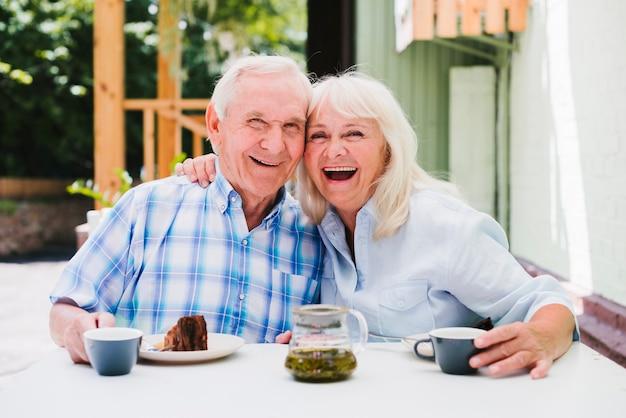 Riendo pareja de ancianos comiendo pastel y bebiendo té Foto gratis