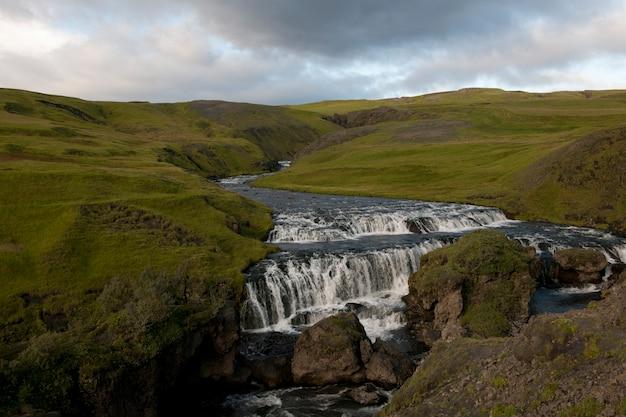 Río erosionado en pastizales montañosos, con escalones de aguas bravas Foto Premium