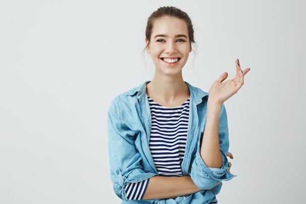 La risa alivia los problemas cotidianos. mujer encantadora en traje de moda con peinado de moño gesticulando mientras habla con un amigo, de pie con la mano cruzada sobre el cuerpo y sonriendo ampliamente Foto gratis