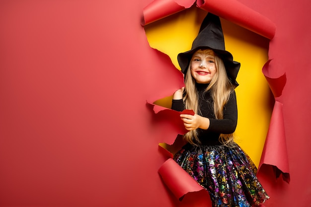 Risa divertida niña en un disfraz de bruja en halloween Foto Premium