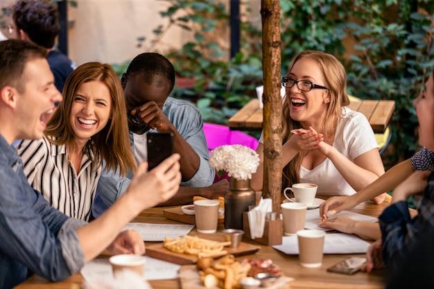 Risa sincera y mostrando una imagen en el teléfono inteligente en la reunión informal con mejores amigos en la terraza del restaurante Foto gratis