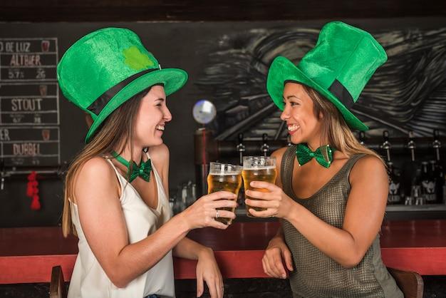 Risas de mujeres jóvenes en los sombreros de san patricio haciendo sonar vasos de bebida en la barra del bar Foto gratis