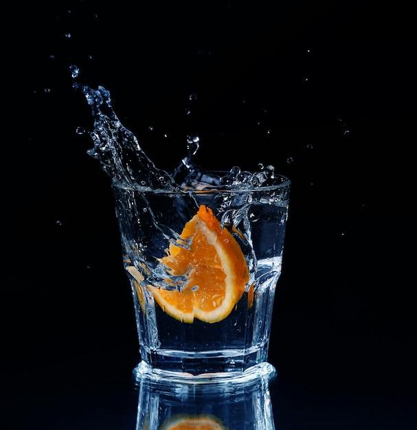 Rodaja de limón chapoteando en un vaso de agua con un chorro de gotas de agua en movimiento suspendido en el aire sobre el vaso sobre un fondo oscuro. Foto Premium