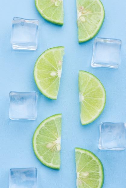 Rodaja de limón fresco con cubito de hielo en azul Foto Premium