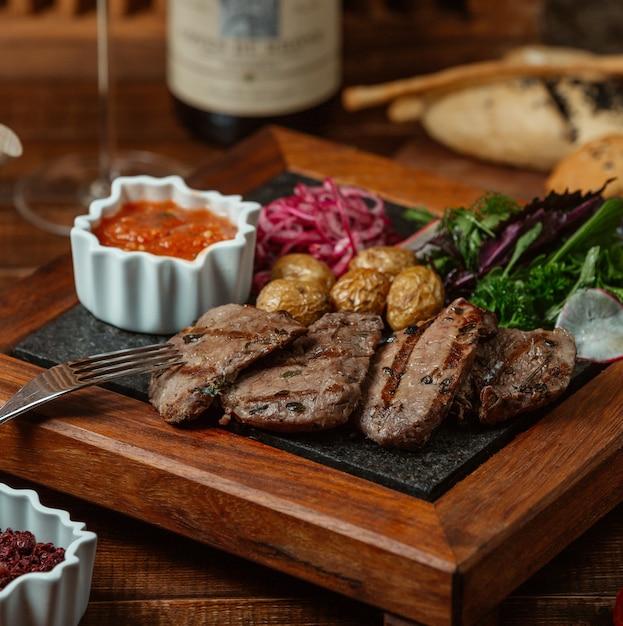 Rodajas de carne marinada a la parrilla servidas con papas baby, cebolla, ensalada de berenjena y hierbas Foto gratis