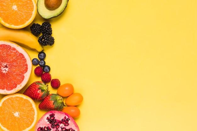 Rodajas de frutas y bayas sobre fondo amarillo Foto gratis