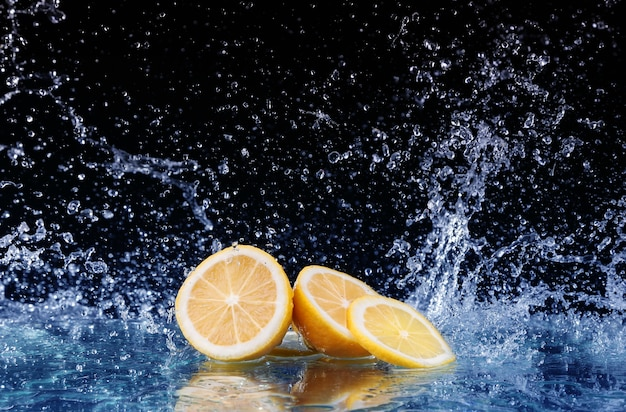 Rodajas de limón en el agua sobre fondo negro Foto Premium