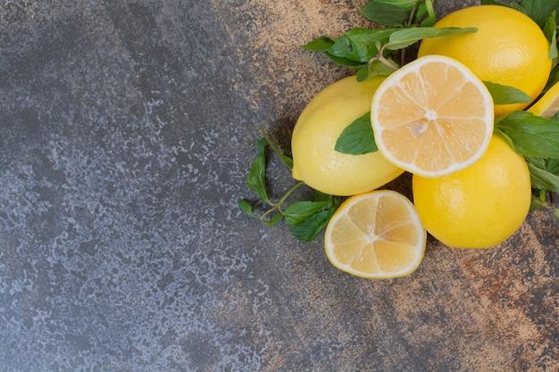 Rodajas de limón con menta sobre superficie de piedra Foto gratis